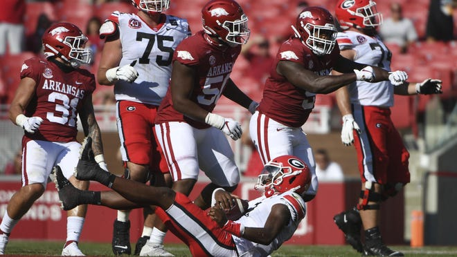 Arkansas defenders Grant Morgan (31), Eric Gregory, (50) and Dorian Gerald (5) celebrate after bringing down Georgia quarterback D'Wan Mathis (2) for a loss during the first half of Saturday's game in Fayetteville.