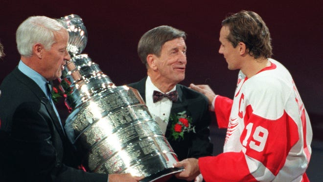 """Oct. 8, 1997: With heavy hearts, Red Wings raise banner. It was as emotional of a night as ever at The Joe. To start the 1997-98 season, the Red Wings hang their first championship banner since 1955. The fans explode when Gordie Howe and Ted Lindsay hand the Stanley Cup to Steve Yzerman. The Captain famously tells Mr. Hockey: """"Thanks for coming."""""""