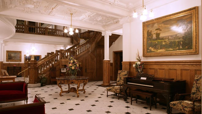 The grand hallway and staircase at Boldt Castle includes a piano.