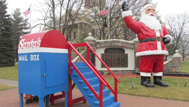 Santa Claus waves to passers-by Tuesday in downtown Mason, inviting children to drop off letters.