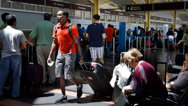 A man walks past people standing in line at Washington's Reagan National Airport after technical issues at a Federal Aviation Administration center in Virginia caused delays on Saturday, Aug. 15, 2015.