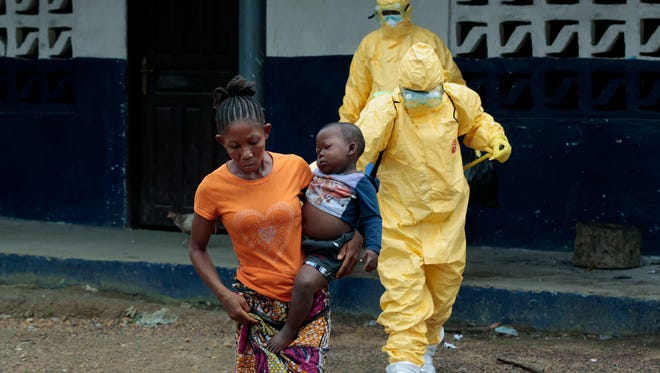 Marie Nyan, 26, whose mother died of Ebola, carries her son Nathaniel Edward, 2, to an ambulance after showing signs of Ebola infection in the village of Freeman Reserve,  Liberia, on Sept. 30, 2014.
