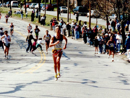 In this April 17, 1995, photo provided by Carol M. Beach, her husband Ben Beach, age 45, runs along the Boston Marathon course in Newton, Mass. Beach, of Bethesda, Md., is looking to be the first person to run the race 50 years in a row on Monday, April 17, 2017.