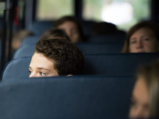 Students ride the bus on the first day of school in