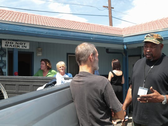 Victor Beecham from Path of Life Ministries talks with Ben Aldridge at City Center Motel in Indio, Calif., Tuesday, May 29, 2018.  Aldridge and nearly 40 others were housed at the hotel after being evicted from land in Coachella.