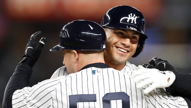Gleyber Torres embraces New York Yankees first base coach Reggie Willits (50) after recording his first major league hit.