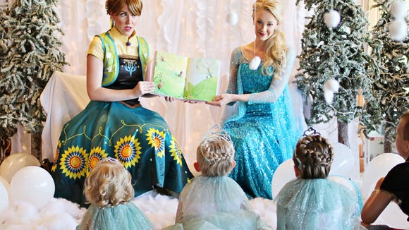 Katie Whited, left, and Jamie Scott read to children at a birthday party.
