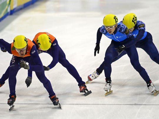 (L-R) Sjinkie Knegt and Niels Kerstholt of the team Netherlands and Victor An and Semen Elistratov of team Russia compete in the men's 5000m relay final race of the ISU European Short Track speed skating Championships in Dresden, eastern Germany, on Jan. 19, 2014.