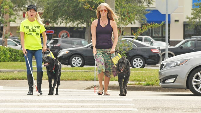 Lori Ciceroni, with her guide dog Gayle, and Jennifer Cleveland, with her guide dog Frank, are seen in 2015 crossing W. New Haven Avenue in West Melbourne. They are both legally blind and have been helped by the Center for the Visually Impaired, which serves Brevard residents.