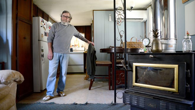 David Cooke stands in his trailer home in Madison County. Although the home needs work, including fixing the wood stove in the living room, Cooke says that he will stay in the rural location for as long as he can because he likes the serenity of the area.