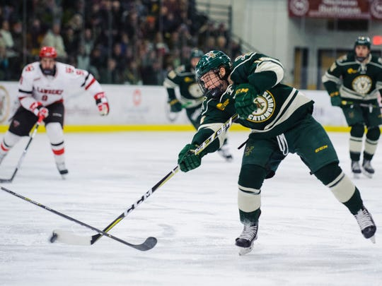 Vermont forward Ace Cowans (14) shoots the puck during