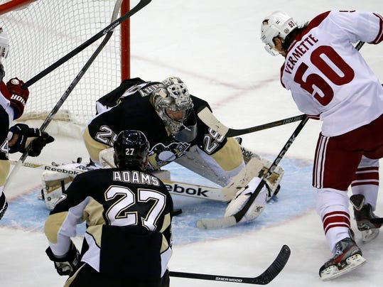 Phoenix Coyotes' Antoine Vermette (50) gets to a loose puck below Pittsburgh Penguins goalie Marc-Andre Fleury (29) for a first-period goal during an NHL hockey game in Pittsburgh, Tuesday, March 25, 2014. (AP Photo/Gene J. Puskar)