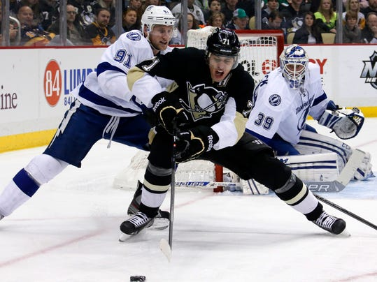 Pittsburgh Penguins' Evgeni Malkin (71) works to control the puck as Tampa Bay Lightning's Steven Stamkos (91) defends in front of Tampa Bay Lightning goalie Anders Lindback (39) in the second period of an NHL hockey game in Pittsburgh, Saturday, March 22, 2014. Malkin had two goals and two assists in the Penguins 4-3 overtime win. (AP Photo/Gene J. Puskar)