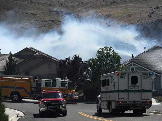 A large brush fire is seen above Caughlin Ranch in