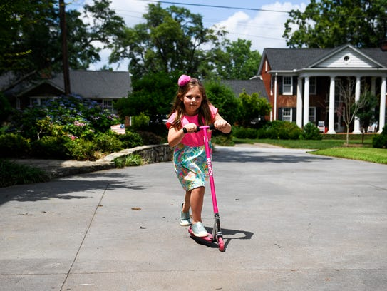 Madison Barber, 7, rides her scooter on Thursday, May
