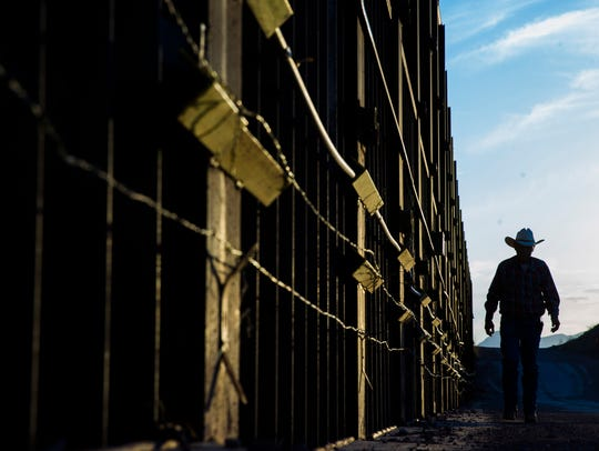Rancher John Ladd walks along the border fence on his