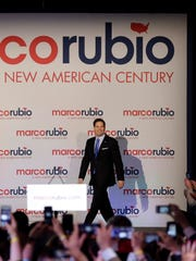 Marco Rubio smiles as he arrives at a rally to launch