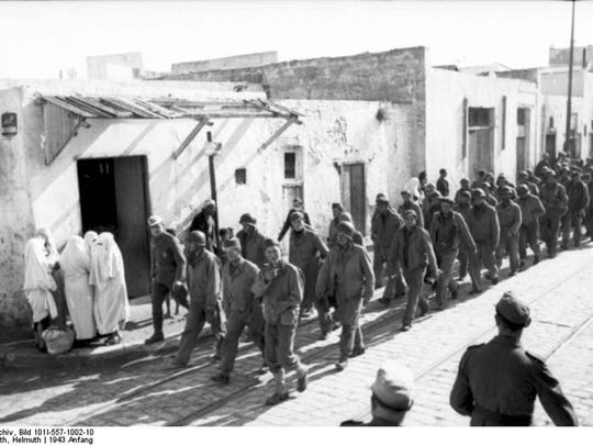 American prisoners of war marching through a Tunisian village during the battle of Kasserine Pass, February 1943.