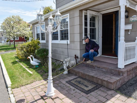 The Tober family of Monmouth Beach, NJ, is one of about 1,200 New Jerseyan applicants who were approved for the RREM program, but later decided to turn down the grant money to fix their Sandy damaged homes. Brian Tober, who grew up in this home, measures how are out new stairs may have to go if certain repairs were made to the house. /Russ DeSantis/Special to the Asbury Park Press / SLUG-ASB 0429 sandy rrem walkaways