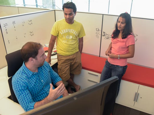 Going over software at Commvault's new headquarters in Tinton Falls are engineers Brent Burd (seated), Robit Dikkar (middle) and Deepadi Shingavi.