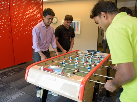 Employees enjoy breaks from work, such as playing foosball, at Commvault's new headquarters in Tinton Falls.