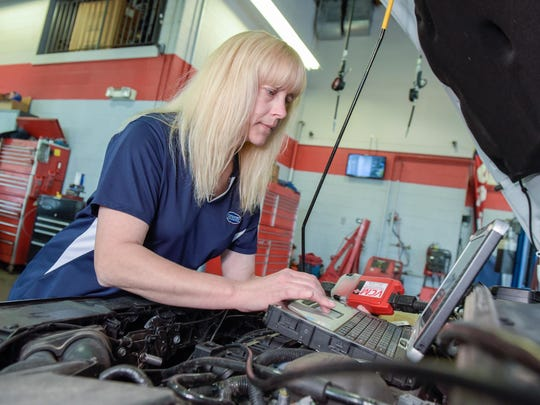 Janet Bigelow uses the Ford factory diagnostic tool, VCM, to scan for trouble codes on a 2015 Ford Focus at Advanced Tire & Auto in Aberdeen.
