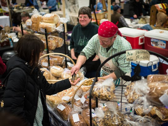 Chuck Sully and his fiance, Jean Truckey, hand out samples of their granola during the New Leaf Winter Farmers Market at the KI Convention Center in downtown Green Bay.