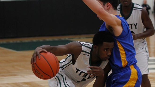 Trinity High School's Tre Ivory (1) fights pressure from Newport Central Catholic's Zach Pangallo (12) during the first half of play at Trinity High School in Louisville, Kentucky.        February 18, 2014