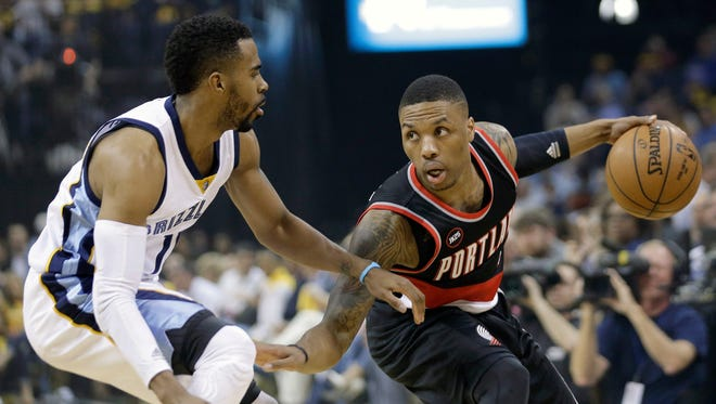 Portland Trail Blazers guard Damian Lillard, right, looks for a way around Memphis Grizzlies guard Mike Conley, left, in the first half of Game 2 of an NBA basketball Western Conference playoff series Wednesday, April 22, 2015, in Memphis, Tenn.