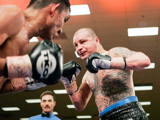 FILE - In this Feb. 23, 2007, file photo, Evaristo Primero, left, from El Paso, Texas, and five-time world champion Johnny Tapia, from Albuquerque, N.M., square off in the eighth round of a scheduled 10-round bout at Isleta Pueblo, N.M. A documentary on the rise and fall of Tapia is slated to air on HBO on Dec. 16. (AP Photo/Jake Schoellkopf, File)