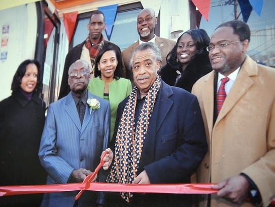 Russell Graddy, second from left, and the Rev. Al Sharpton, with scissors, in an undated photograph hanging in Graddy's office that was taken during a ribbon-cutting ceremony at Mr. G's.