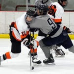 Northville's Sam Bradley run into a check by Farmington's Tanner Neill in the season opener Friday at Novi Ice Arena.