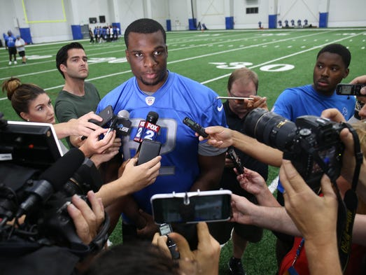 Detroit Lions lineman Cyrus Kouandjio talks with reporters