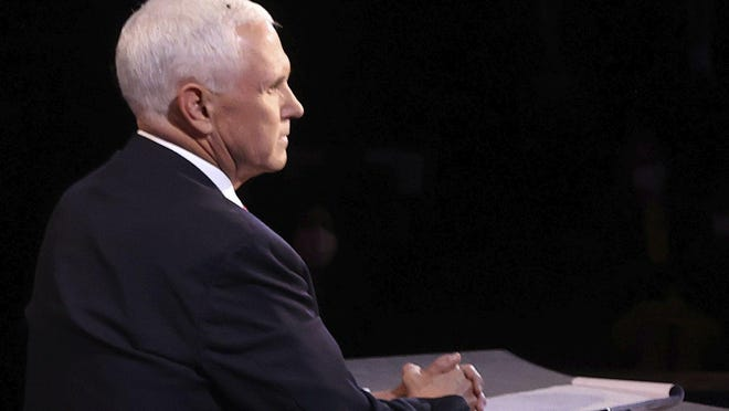 A fly lands on the head of Vice President Mike Pence during the vice presidential debate on Oct. 7 at the University of Utah in Salt Lake City.