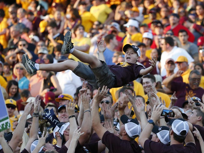 Arizona State Sun Devils fans toss a young fan after