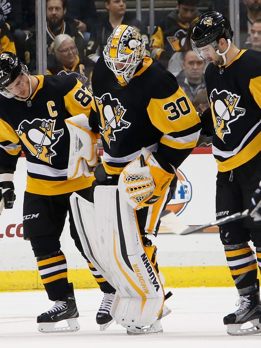 Pittsburgh Penguins goalie Matt Murray (30) is helped off the ice by Sidney Crosby (87) and Justin Schultz (4) after being involved in a collision with Philadelphia Flyers' Jakub Voracek in the second period of an NHL hockey game in Pittsburgh, Monday, Nov. 27, 2017. (AP Photo/Gene J. Puskar)