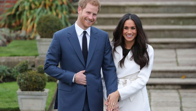 Britain's Prince Harry and his fiancée, American actress Meghan Markle, pose for a photograph in the Sunken Garden at Kensington Palace in west London on Monday, following the announcement of their engagement.