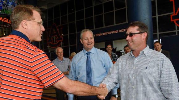 New Auburn baseball coach Butch Thompson shakes hands with Auburn football coach Gus Malzahn Thursday as Tigers athletics director Jay Jacobs looks on.