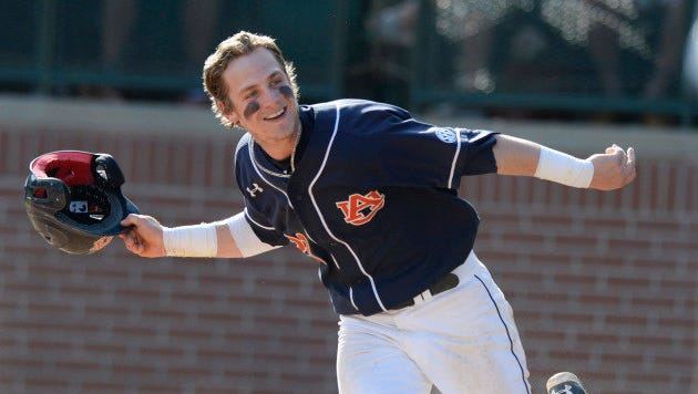 Jordan Ebert (23) tosses his helmet into the dugout to go celebrate with the team after he scored the game-winning run off of Ryan Tella's walk-off single.Mercer vs Auburn in Auburn, Ala. on Sunday, March 9, 2014.Zach Bland