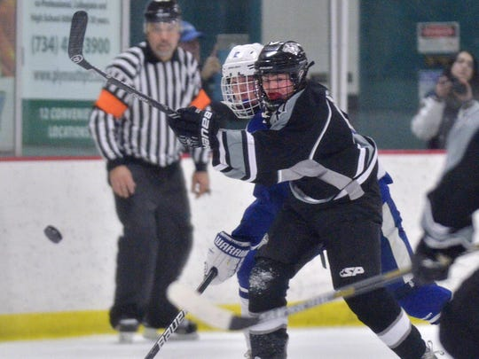 Watching the puck go by are Plymouth's Jack Balch (No.