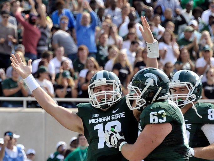 Michigan State quarterback Connor Cook, left, celebrates his first-quarter touchdown with Travis Jackson, center, and Josiah Price  against Eastern Michigan on Saturday, Sept. 20, 2014, at Spartan Stadium in East Lansing. MSU won, 73-14.