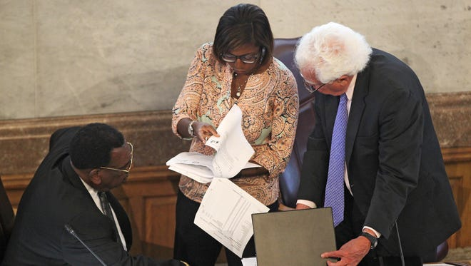 Cincinnati City Council members Wendell Young, Yvette Simpson and David Mann review documents prior to the budget and finance committee meeting. The city of Cincinnati is headed for a government shutdown after four members of City Council refused Monday to support a capital budget plan that fixes roads and the city's fleet. Against the capital plan: P.G. Sittenfeld, Mann, Young and Simpson.