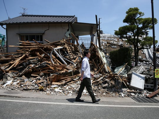 A man walks past the rubble of a collapsed house  following
