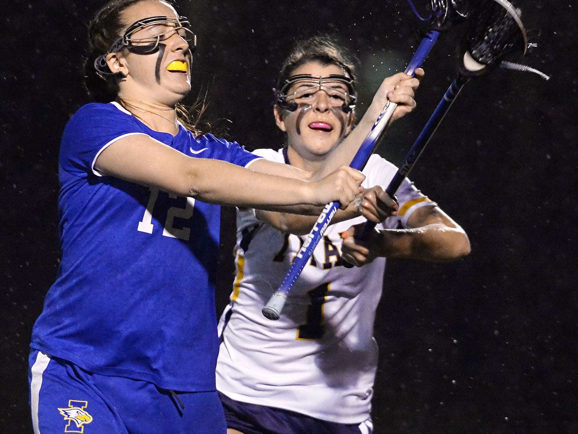 Irondequoit's Ari Torpey, left, gets a pass away while pressured by Webster Thomas' Mackenzie Travis.