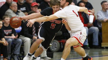 East's Thomas Dunbar(1), right, attempts steal the ball against Medford's Cameron Wenzel(5) during Thursday night Division 2 boys basketball sectional semifinal at Merrill High School.