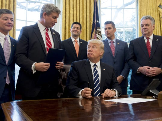 US President Donald Trump speaks with Representative Bill Huizenga (2nd L), Republican of Michigan, before signing House Joint Resolution 41, which removes some Dodd-Frank regulations on oil and gas companies, during a bill signing ceremony in the Oval Office of the White House in Washington, DC, February 14, 2017
