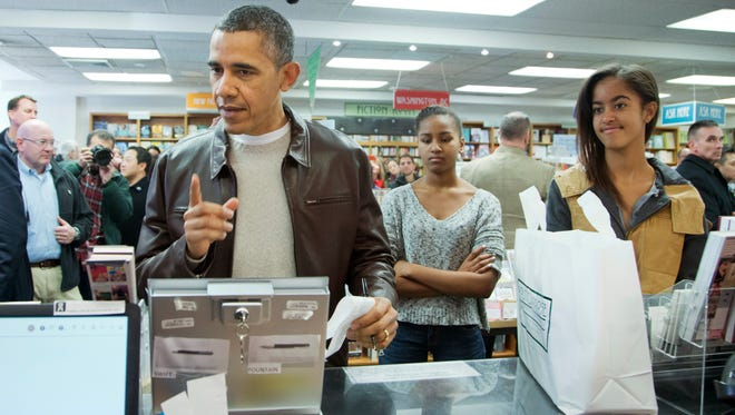 President Barack Obama, with daughters Sasha, center, and Malia, pays for his purchase the the local bookstore Politics and Prose in northwest Washington.