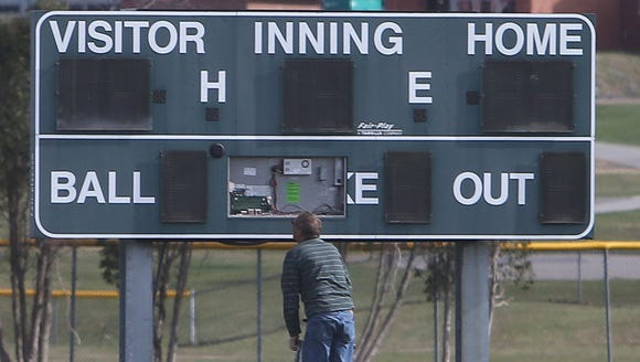 A scoreboard is repaired on during a softball game