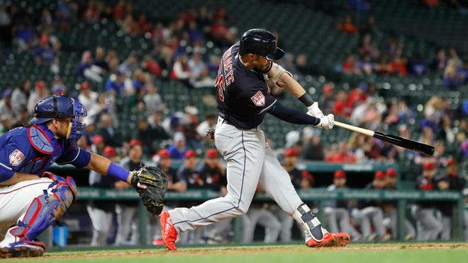 Cleveland Indians Eric Stamets (66) swings for a grand slam in front of Texas Rangers catcher Jeff Mathis (2) during the fourth inning of an exhibition baseball game in Arlington, Texas, Monday, March 25, 2019. (AP Photo/LM Otero)