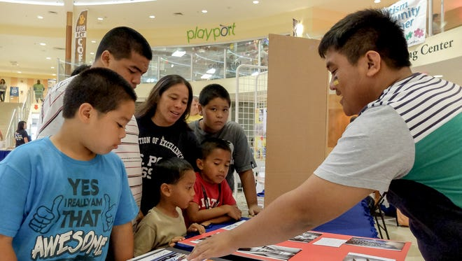 In this April 4, 2015, file photo, Gian Magana, right, who has autism, explains his photographic techniques to a family during the 8th annual Autism Awareness Fair at the Agana Shopping Center.
